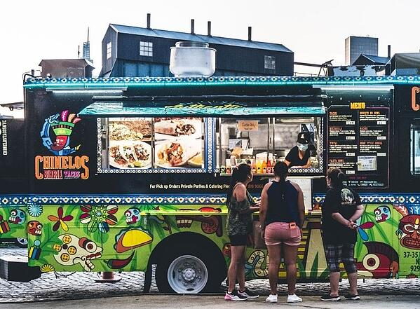 People standing outside taco truck_Photo by Harry Gillen on Unsplash