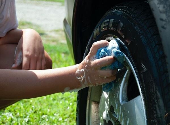 Cleaning hubcaps to remove dirt before vinyl wrap application - Photo by Elly Johnson on Unsplash