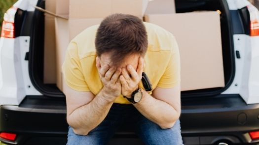 Vehicle wrapping mistakes - a man sits in the back of his van with his head in his hands