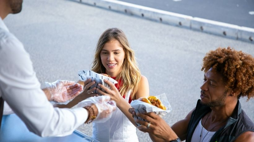Investing in a food truck - man serving customers with food